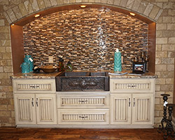 Tuscany kitchen with a splash of stone and glass mosaic to enhance the painted cabinets set about an acacia handscraped floor.